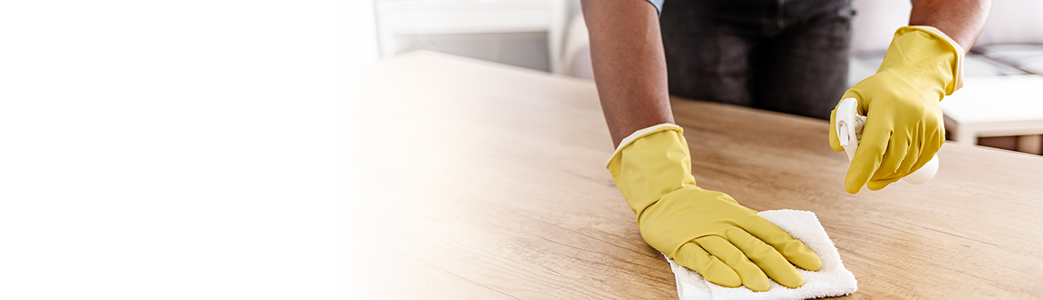 Hands wearing a pair of yellow rubber gloves, holding a spray bottle and wiping a surface with a rag